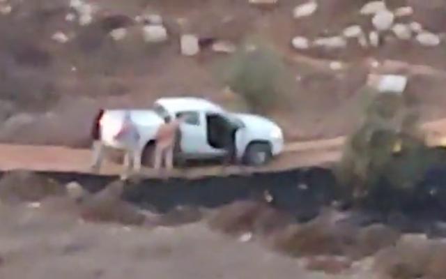 مستوطنون إسرائيليون يحيطون بسيارة تابعة للجيش الإسرائيلي بالقرب من مستوطنة عادي عاد، 13 أكتوبر، 2021 (فيديو / courtesy)
