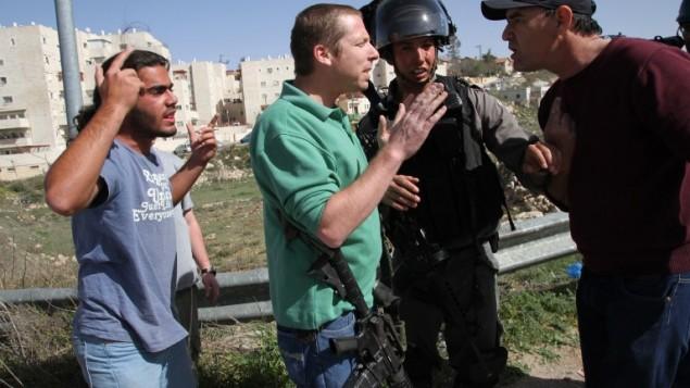 مصور وصحفي فرانس برس عباس مومني يناقش قوات الامن الاسرائيلية بعد أن قام المستوطنون بالقاء الحجارة على سيارته 7 مارس 2014 (أ ف ب/ اس تي أر )