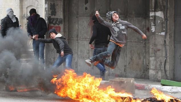 اشتباكات بين فلسطينيون والجيش الاسرائيلي (غير مرئي في الصورة) في الخليل ١٧ مارس ٢٠١٤ (بعدسة حازم بدر/ أ ف ب)
