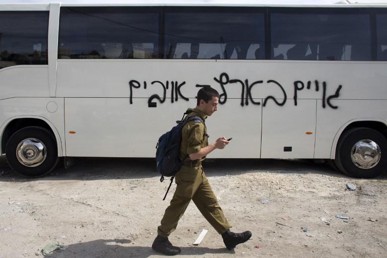 """جندي اسرائيلي يعبر امام باص كتب عليه مخربون """"الغير يهودي في اسرائيل هو العدو"""" في هجوم دفع الثمن 24 مارس 2014 (أحمد غرابلي / أ ف ب)"""