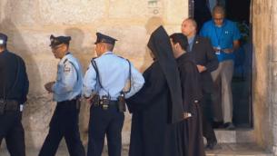 كهنة ورجال شرطة سوية امام كنيسة القيامة في البلدة القديمة, القدس  (screen capture: GPO)