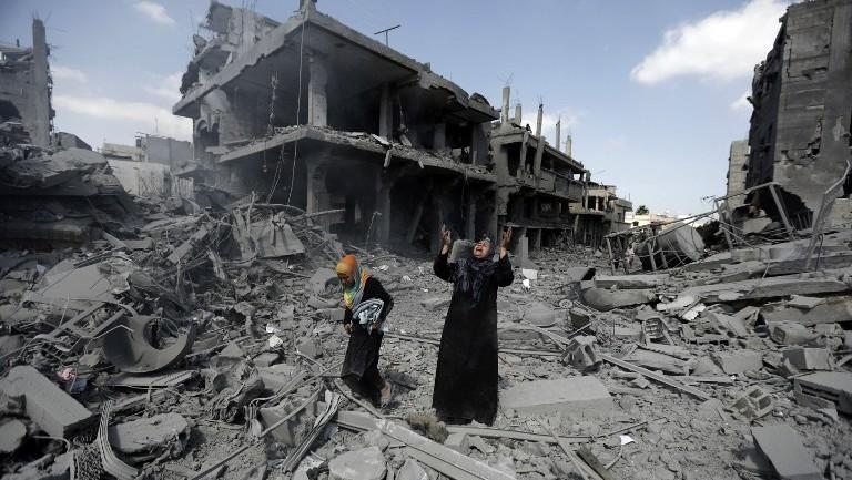امرأة فلسطينية وسط المباني المدمرة في منطقة شمال بيت حانون في قطاع غزة  26 يوليو 2014. AFP PHOTO / MOHAMMED ABED