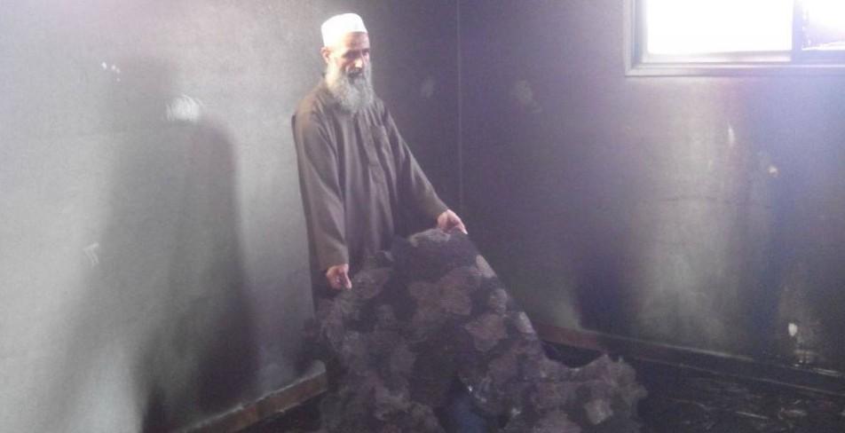 """رجل مسلم يعرض اضرار الحريق للمشجد الذي تعرض لهجوم ما يسمى """"تدفيع الثمن"""" في الضفة الغربية 14 اوكتوبر 2014 (مقدمة من حاخامات من اجل حقوق الانسان)"""