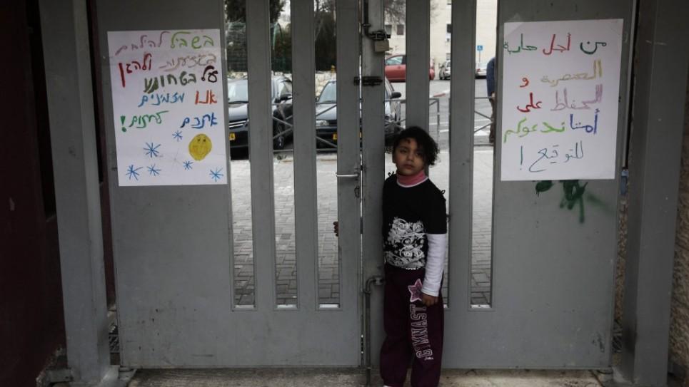 تلميذة عربية تقف امام بوابة المدرسة الغربية اليهودية يد بيد (فلاش 90)
