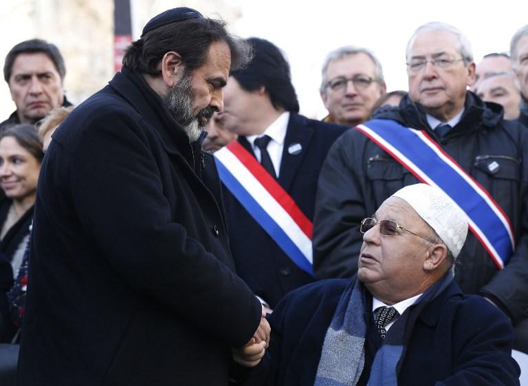 """جويل ميرغوي، رئيس الكنيس اليهودي المركزي في فرنسا (L) يصافح رئيس جامعة  """"المسجد الكبير"""" في باريس دليل بوبكر خلال المسيرة الجمهورية 11 يناير 2015 . AFP PHOTO / THOMAS SAMSON"""