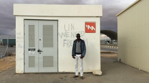 """معتصم علي يقف امام صندوق كهربائي في حولوت، كتب المعتقلون عليه """"الأمم المتحدة، نحن بحاجة للحرية"""". (Debra Kamin/Times of Israel)"""