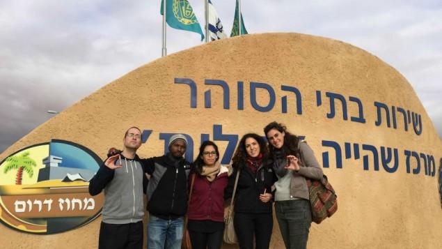 اليوت غلاسينبرغ، اقصى اليسار، يقف مع لاجئين وناشطين في مدخل حولوت ، السبت، 17 يناير 2015 (Debra Kamin/Times of Israel)