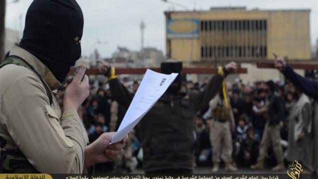 مقاتل من الدولة الاسلامية تهم بالسرقة ضد رجلان مصلوبان في الخلفية (فيسبوك)