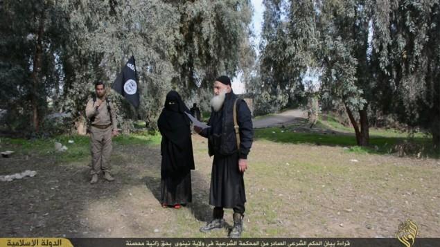 اعضاء في الدولة الاسلامية يقودون امرأة محجبة للرجم بالحجارة بتهمة الزنى (فيسبوك)
