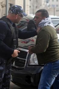 شرطي فلسطيني يوقف أحد المتظاهرين بعد رشق شبان فلسطينيون غاضبون البيض على موكب وزير الخارجية الكندي جون بيرد في رام الله يوم الأحد 18 يناير، 2015    AFP/ABBAS MOMANI