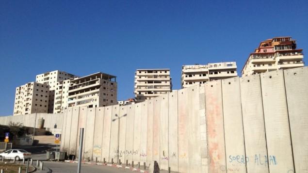 مباني سكنية في راس خميس تعلو فوق الجدار في القدس الشرقية (Elhanan Miller/Times of Israel)