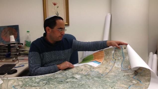 ديفيد كورن يعرض خريطة لحدود  القدس في مكتبه في قاعة بلدية المدينة، 18 فبراير 2015 (بعدسة الحانان ميلر/ فلاش 90)