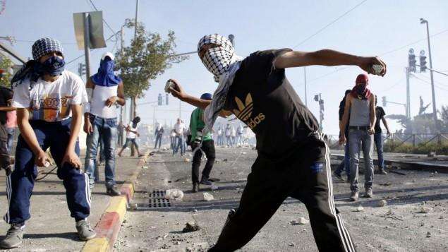 ملثمون فلسطينيون يرمون الحجارة اثناء اشتباكات مع الشرطة الاسرائيلية في مخيم شعفاط في القدس الشرقية (Sliman Khader/Flash90)
