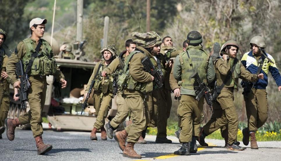 جنود الجيش الإسرائيلي يحملون رفيقهم المصاب بعد اصابة صاروخ مضاد للدبابات لمركبة تابعة للجيش في منطقة تقع على الحدود مع لبنان، 28 يناير 2015 (Basal Awidat/Flash90)