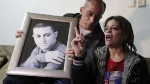 والدي محمد مسلم، الشاب العربي من بيت حنينا في القدس الشرقية الذي اعدمه تنظيم الدولة الإسلامية بتهمة التجسس لصالح اسرائيل، يعرضون صورة ابنهم 10 مارس 2015 ( AFP / AHMAD GHARABLI)
