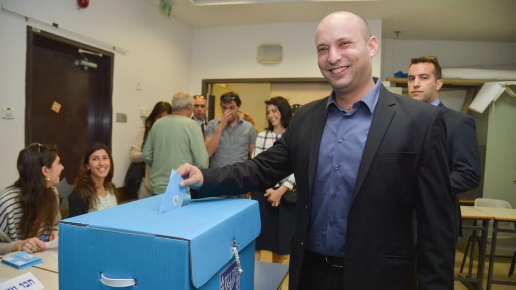 رئيس حزب البيت اليهودي نفتالي بينيت يضع صوته في صندوق اقتراع في رعنانا، 17 مارس 2015 (Flash90)