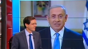 رئيس الوزراء بنيامين نتنياهو يتحدث مع القناة الثانية بينما يجلس رئيس المعسكر الصهيوني يتسحاك هرتسوغ في الاستوديو، 14 مارس 2015 (Channel 2 News)