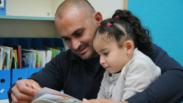 أب يقرأ قصة لطفلته في باقة الغربية. (Akmal Nagnagy)