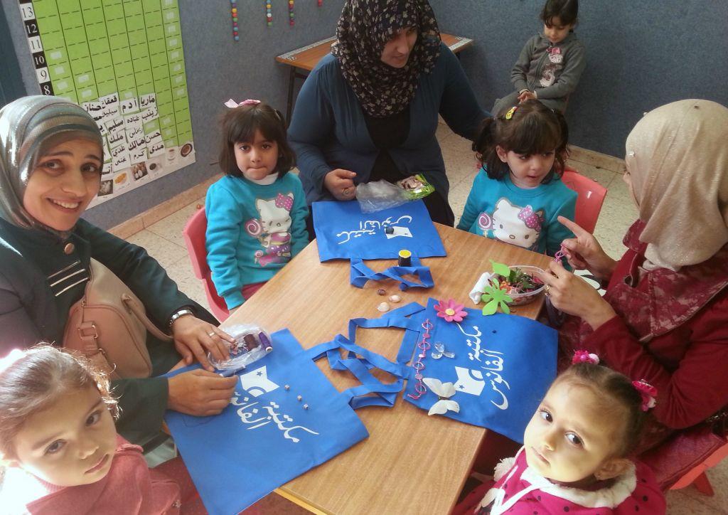 """أمهات وأطفال يزينون حقائب لكتب """"مكتبة الفانوس"""" في روضة في أم الفحم. (Amna Jabareen)"""