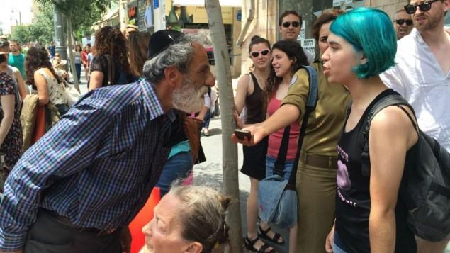 """مواجهة بين رجل وإحدى المشاركات في """"مسيرة الشراميط""""، 29 مايو، 2015. (Renee Ghert-Zand/Times of Israel)"""