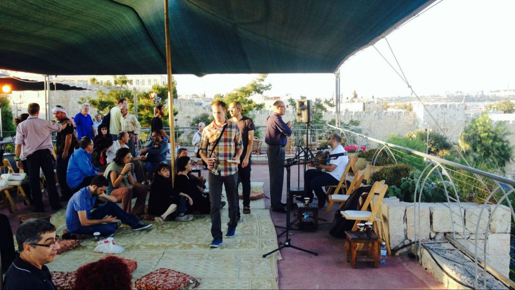في شهر سبتمبر، تجمع عدد من الاشخاص لسماع المؤذن عن طريق غناء وتفسير حاخام وشيخ في مهرجان الموسيقى المقدسة (Jessica Steinberg/Times of Israel)