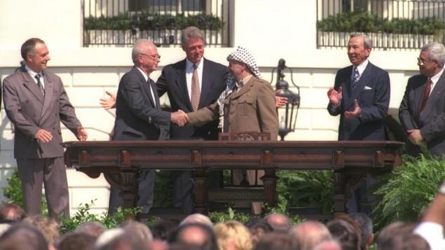 بيل كلينتون ينظر إلى يتسحاق رابين وياسر عرفات وهما يتصافحان خلال التوقيع التاريخي على إتفاق أوسلو، 13 سبتمبر، 1993. على أقصى اليمين، الزعيم الفلسطيني الحالي محمود عباس. (GPO)