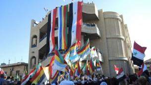 أعلام سورية ودرزية في تظاهرة مؤيدة للأسد في قرية مجدل شمس الدرزية في هضبة الجولان يوم الإثنين. (Melanie Lidman/Times of Israel)