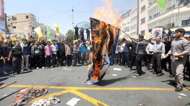 متظاهرون إيرانيون يحرقون العلم الإسرائيلي خلال تظاهرة  بمناسبة يوم القدس العالمي في طهران، 10 يوليو، 2015. (AFP PHOTO / ATTA KENARE)