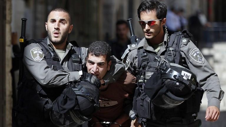 قوات الأمن الإسرائيلية تعتقل رجل فلسطيني خلال اشتباكات بين متظاهرين فلسطينيين والشرطة الإسرائيلية في البلدة القديمة في القدس، 26 يوليو 2015 (AFP PHOTO / AHMAD GHARABLI)