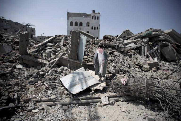 رجل فلسطيني، مغطى بالعلم الفلسطيني، يتفحص أنقاض البنايات والمنازل في حي الشجاعية في مدينة غزة، في 20 يوليو، 2014. (AFP PHOTO/MAHMUD HAMS)
