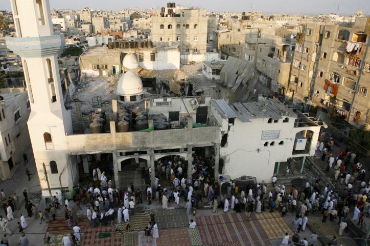 فلسطينيون خلال صلاة عيد الفطر في مسجد الفاروق الذي دُمر قبل أسبوع من ذلك في غارة جوية إسرائيلية على رفح، جنوب قطاع غزة، 28 يوليو. (Abed Rahim Khatib/Flash90)
