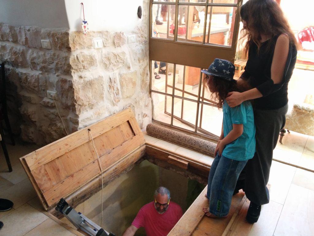 أفراد عائلة شيمشوني يقفون عند حماس طقوسي يهودي من القرن الأول في منزل العائلة  في عين كيريم، 1 يوليو، 2015. (Ilan Ben Zion/Times of Israel staff)