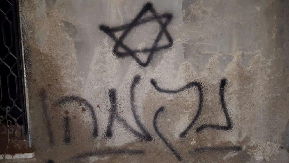 """نجمة داوود وكلمة """"انتقام"""" باللغة العبرية على حائط منزل عائلة دوابشة المحروق في بلدة دوما الفلسطينية بالقرب من نابلس، 331 يوليو 2015 (Zacharia Sadeh/Rabbis for Human Rights)"""