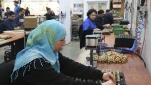 امرأة فلسطينية تعمل في مصنع صودا ستريم في مستوطنة ميشور ادوميم في الضفة الغربية، 2 فبراير 2014 (Nati Shohat/Flash90)