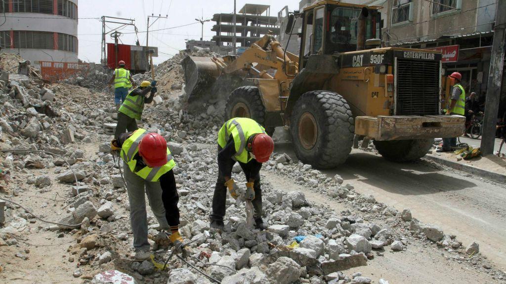 """عمال فلسطينيون يعملون على إعادة بناء مركز تجاري، دمره القصف الإسرائيلي خلال عملية """"الجرف الصامد""""، في رفح جنوب قطاع غزة، في 20 أبريل، 2015. أعمال إعادة الإعمار ممولة من برنامج الأمم المتحدة الإنمائي. (Abed Rahim Khatib/Flash 90)"""