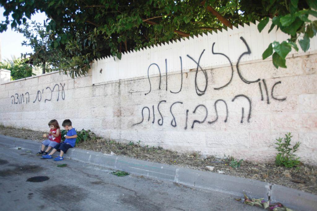 """اطفال يجلسون امام جدار مكتوب عليه الشعارات العنصرية """"العنصرية او الاختلاط"""" و""""العرب الى الخارج"""" في ابو غوش، 18 يونيو 2013 (Flash90)"""