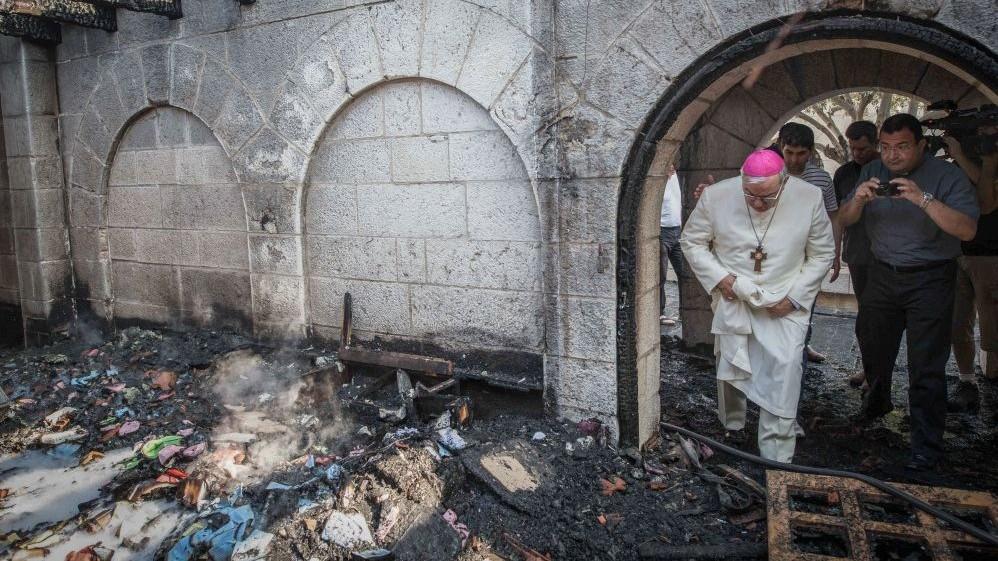 خوري يتفحص اضرار الحريق في كنيسة الطابغة على ضفاف بحيرة طبريا في اسرائيل، 18 يونيو 2015 (Basel Awidat/Flash90)
