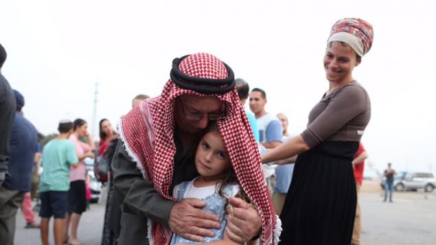 الشيخ إبراهيم أحمد أبو الحوا يححضن طفلة اسرائيلية خلال صلاة في مفترق غوش عتسيون من اجل عائلة دوابشة، 2 اغسطس 2015 (Nati Shohat/Flash90)