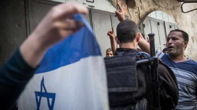 نشطاء من اليهمين اليهودي ومحتجون فلسطينيون، تفصل بينهم الشرطة الإسرائيلية، في مواجهة خلال تظاهرة خارج باحة الحرم القدسي، 9 أغسطس، 2015. (Hadas Parush/Flash90)