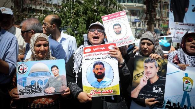 متظاهرون يرفعون صورة الأسير الفلسطيني محمد علان خلال مظاهرة في رام الله، 11 اغسطس 2015 (Flash90)