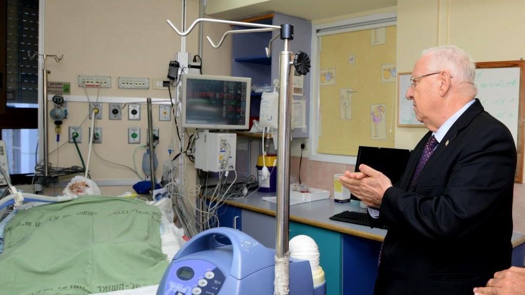 الرئيس رؤوفن ريفلين يزور احمد دوابشة في المستشفى، 31 يوليو 2015 (Mark Neyman/GPO)