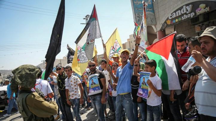 جنود اسرائيليون يواجهون متظاهرين يوقفون السير في طريق مجاورة لبلدة الاسير محمد علان الفلسطيني المضرب عن الطعام بالقرب من نابلس، 15 اغسطس 2015 (Flash90)