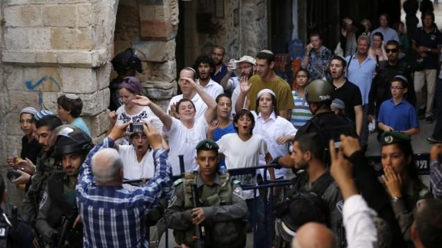 قوات الامن تحرس مجموعة شبان يهود اثناء خروجهم بعد زيارة الحرم القدسي، 13 سبتمبر 2015 (AFP/AHMAD GHARABLI)