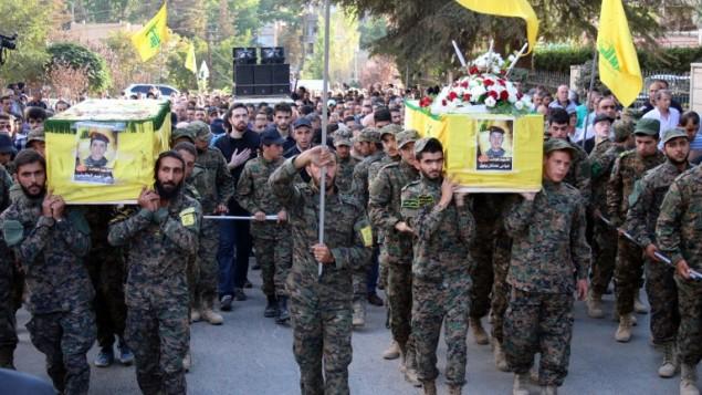 مقاتلو حزب الله يحملون نعوش رفاقهم الذين قُتلوا في المعارك في سوريا خلال جنازتهم في 21 سبتمبر، 2015 في مدينة بعلبك بوادي البقاع شرقي لبنان. (AFP/STR)