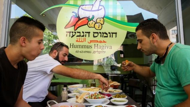 فلسطينيون يتناولون الحمص في مطعم حمص فلسطيني في حي يهودي في القدس، 27 مايو 2015 (Nati Shohat/Flash90)