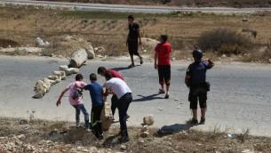 فلسطينيون يستخدمون الصخور لسد شارع في النبي صالح خلال مظاهرة، 28 اغسطس 2015 (Eric Cortellessa/Times of Israel)