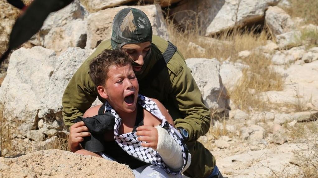 جندي اسرائيلي يحاول اعتقال طفل عمره 12 عاما، مشتبه بالقاء الحجارة، في المظاهرة الاسبوعية في النبي صالح في الضفة الغربية، 28 اغسطس 2015 (Eric Cortellessa/ Times of Israel)