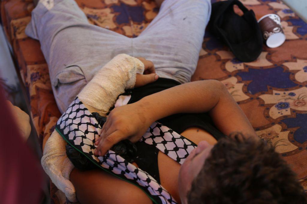 طفل فلسطيني عمره 12 عاما يستلقي في منزله في النبي صالح بعد منع الفلسطينيين جندي اسرائيلي من اعتقاله، 28 اغسطس 2015 (Eric Cortellessa/Times of Israel)