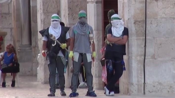 صورة ملتقطة من شريط فيديو نشره الناطق باسم الشرطة فيه يظهر ملثمين فلسطينيين يزعم انهم يتهيؤون لمواجهة قوات الأمن الإسرائيلية في الحرم القدسي، 13 سبتمبر 2015 (screen capture: Israel Police)