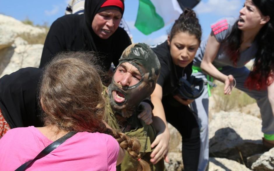 فلسطينيات يصارعن جندي اسرائيلي لمنعه من اعتقال طفل عمره 12 عاما يده مضمدة بالجبصين مشتبه بإلقاء الحجارة، 28 اغسطس 2015 (Eric Cortellessa/Times of Israel)